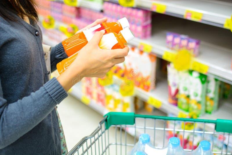Девушка сравнивая в супермаркете стоковая фотография rf