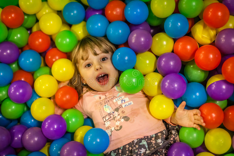 Девушка среди красочных шариков стоковые фотографии rf