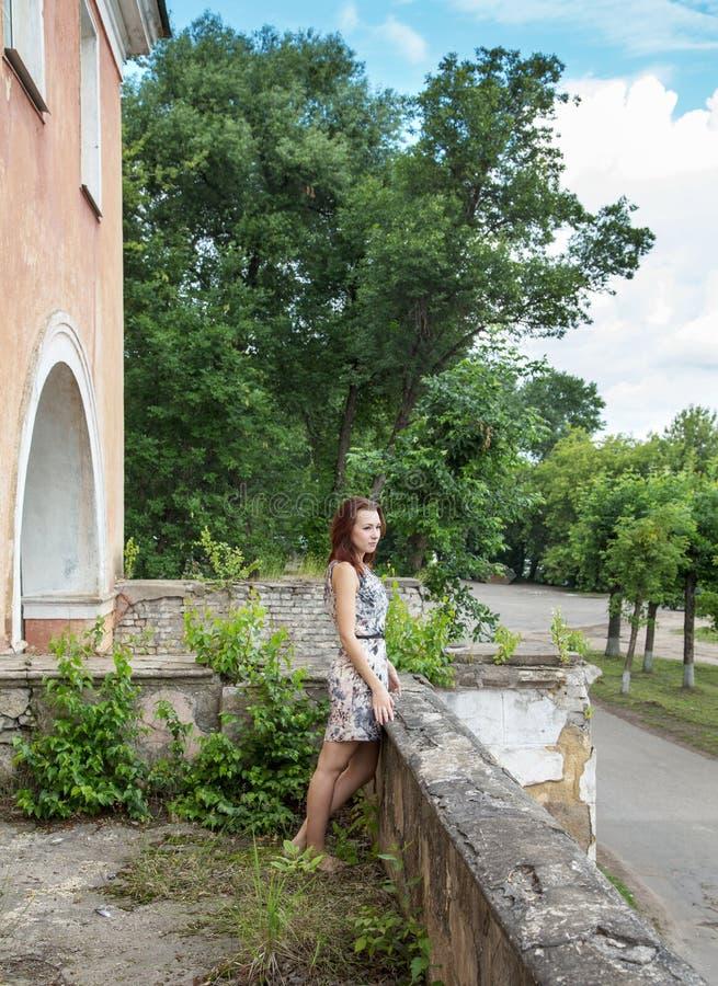 Девушка стоит на балконе старого здания стоковая фотография rf