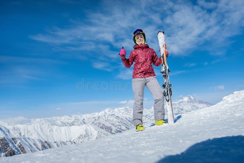 Девушка стоит на наклоне с горными лыжами Показывает большой палец руки стоковые фотографии rf