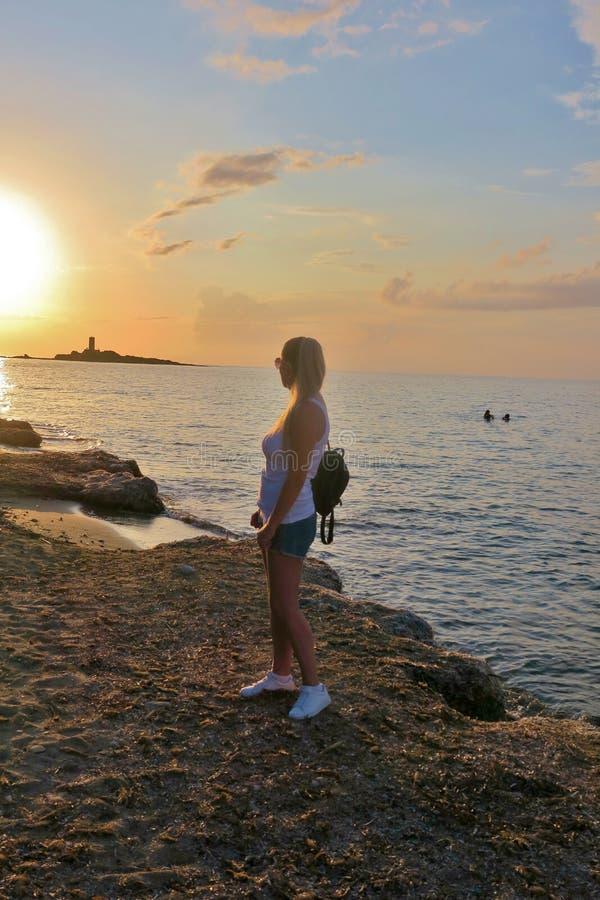 Девушка стоит на seashore и взглядах на красивом заходе солнца стоковые изображения rf