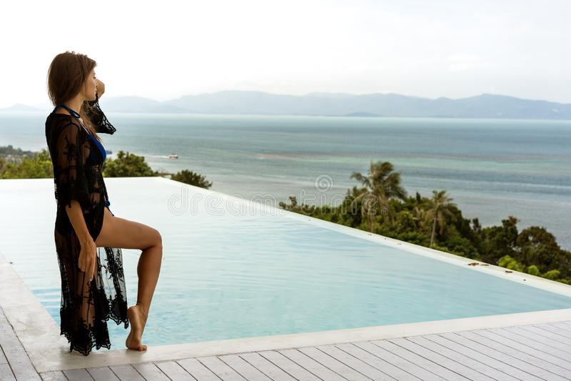 Девушка стоит на seashore обозревая горы около бассейна стоковые фотографии rf