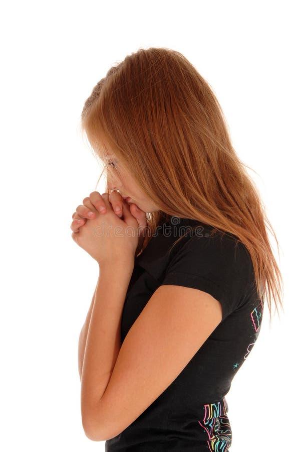Девушка стоя в профиле и моля стоковое фото