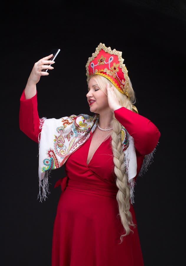 Девушка стоя в русском традиционном костюме с мобильным телефоном стоковые фото