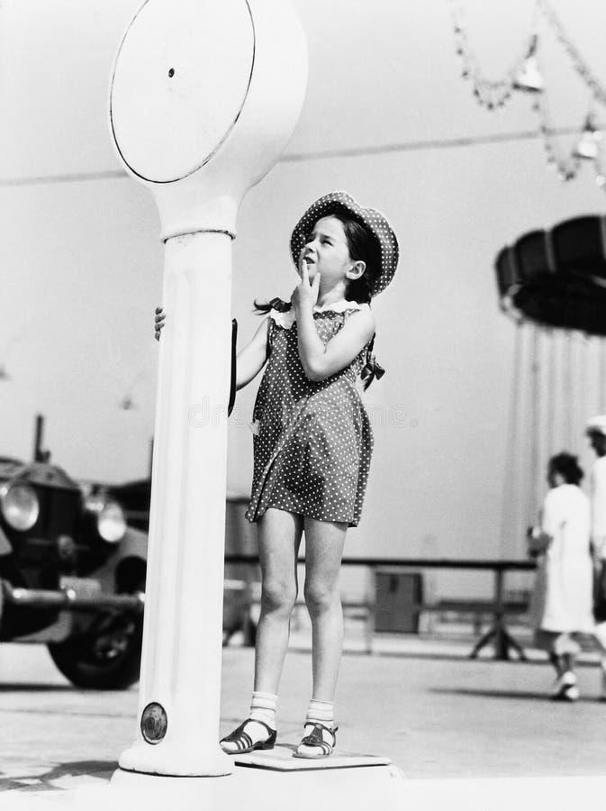 Девушка стоя на веся масштабе (все показанные люди более длинные живущие и никакое имущество не существует Гарантии поставщика ко стоковая фотография rf