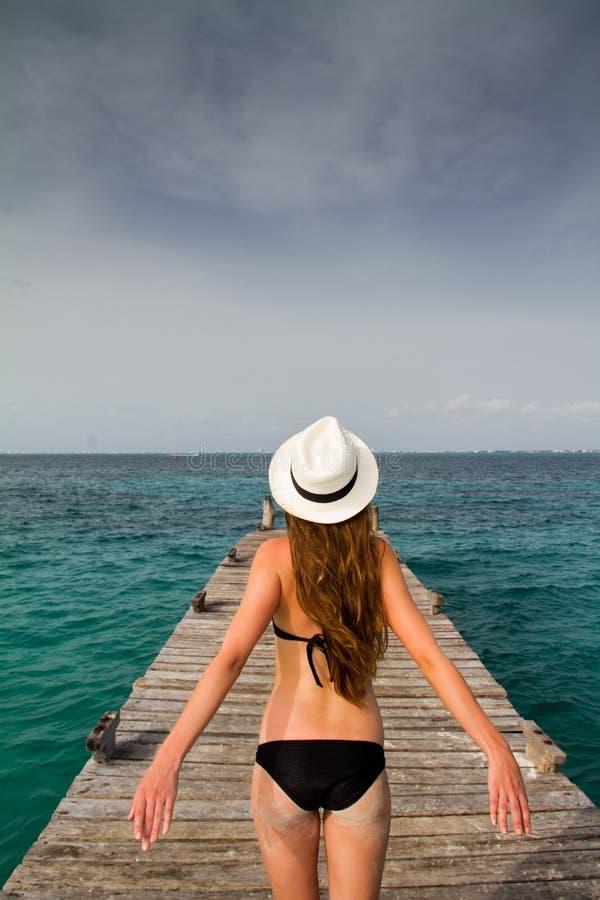 Девушка стоя на пристани наслаждаясь ветерком от моря стоковое изображение