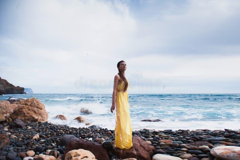 Девушка стоя на пляже против неба и моря стоковая фотография rf