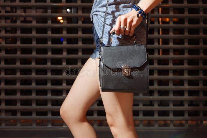 Девушка стоя перед решеткой загородки металла с малой модной сумкой в демикотоне замыкает накоротко стоковая фотография rf