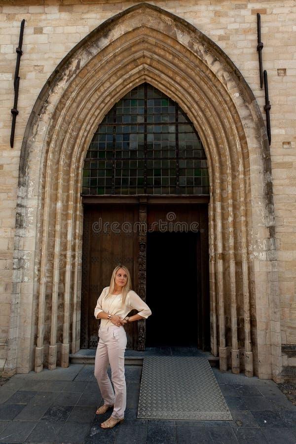 Девушка стоя церковь деревянной двери готическая стоковые фотографии rf
