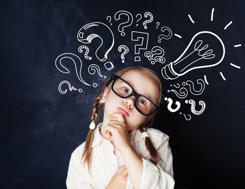 Девушка студента начальной школы с вопросительными знаками стоковые фото