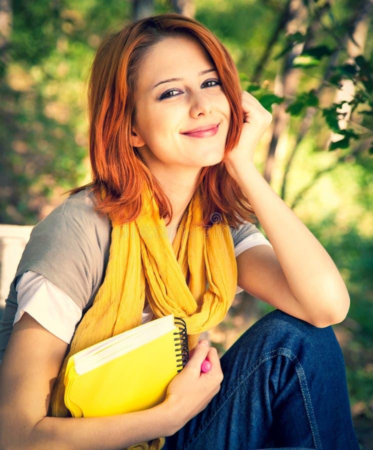 Девушка студента при тетрадь сидя на внешнем стоковая фотография rf