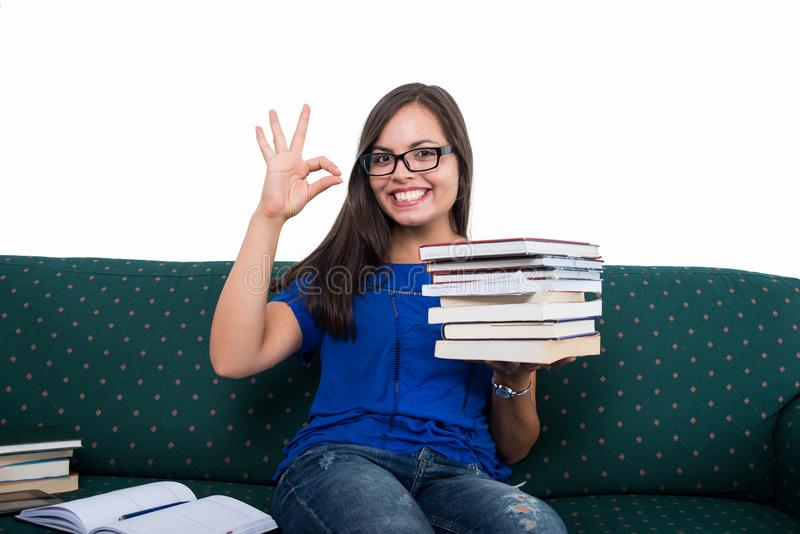 Девушка студента сидя на кресле показывая о'кеы держать записывает стоковое фото