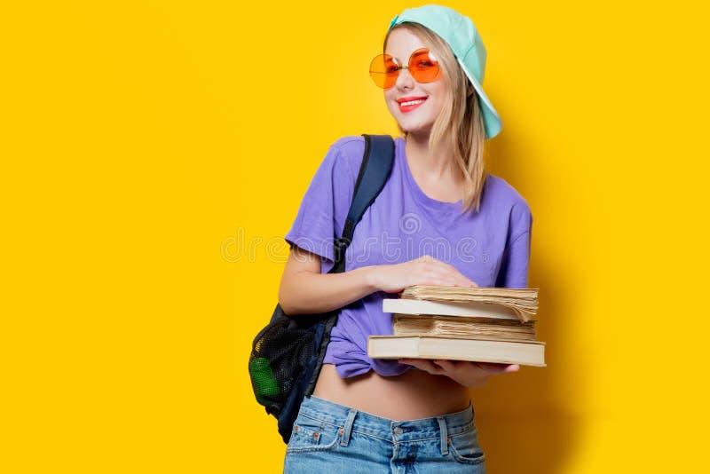 Девушка студента с оранжевыми стеклами и книгами стоковое фото rf