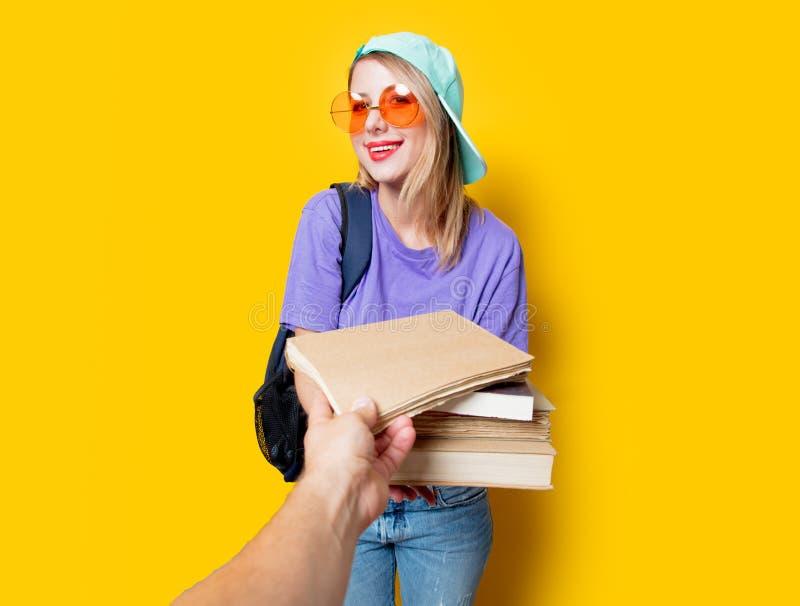 Девушка студента с оранжевыми стеклами и книгами стоковое изображение rf