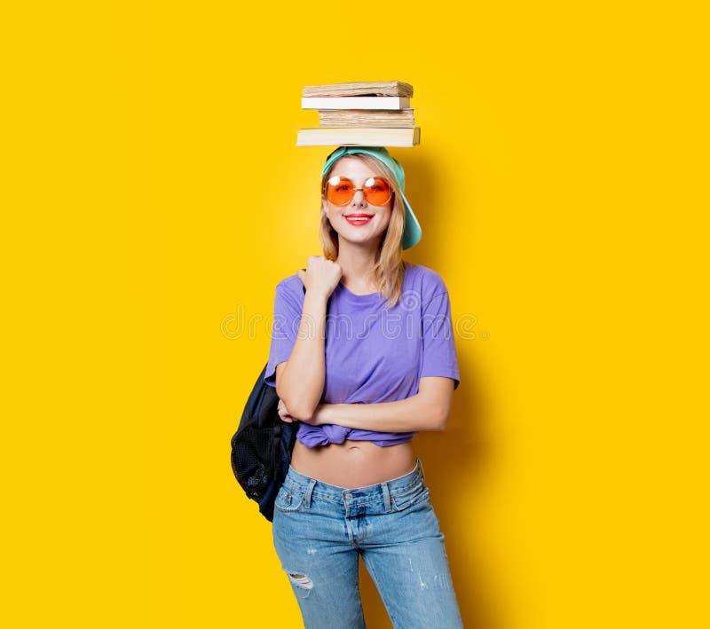 Девушка студента с оранжевыми стеклами и книгами стоковое изображение