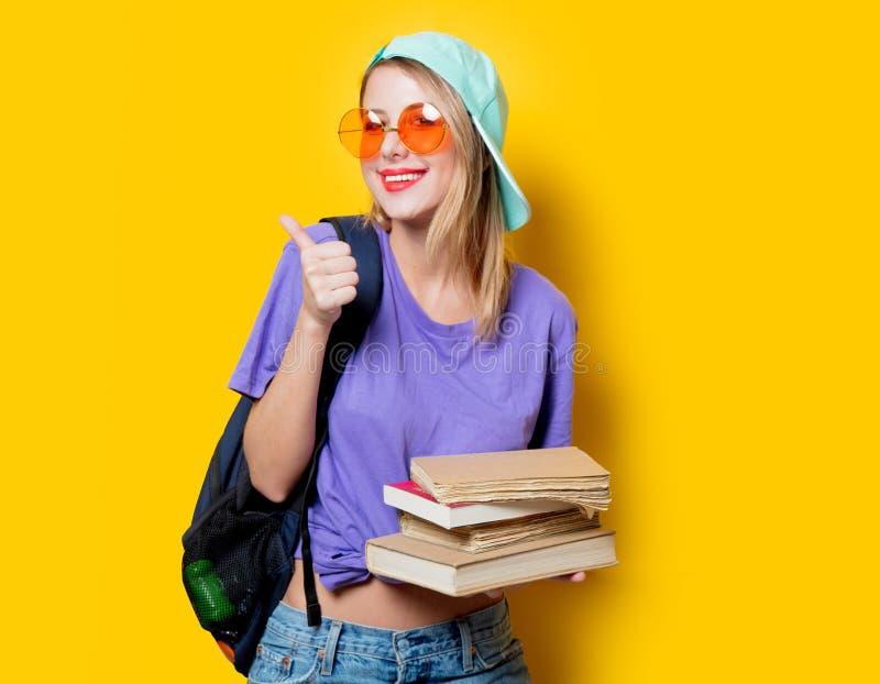 Девушка студента с оранжевыми стеклами и книгами стоковые изображения