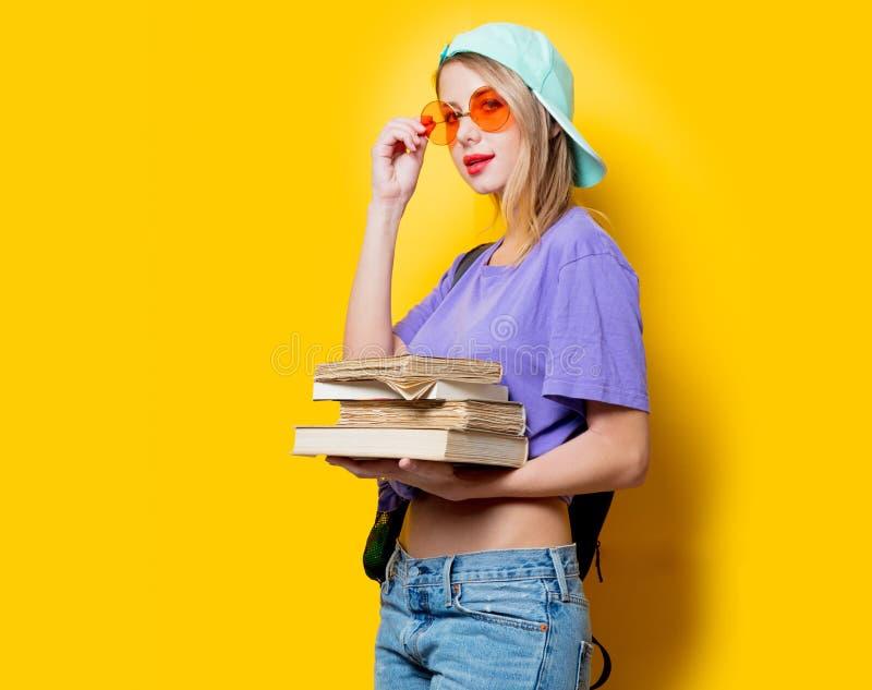 Девушка студента с оранжевыми стеклами и книгами стоковые фото