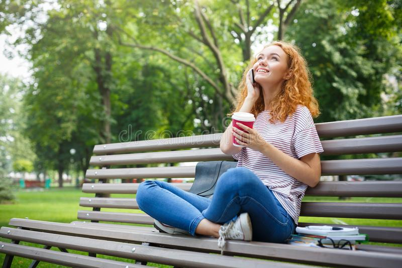 Девушка студента Redhead говоря на мобильном телефоне, выпивая coffe сидя outdoors стоковое изображение