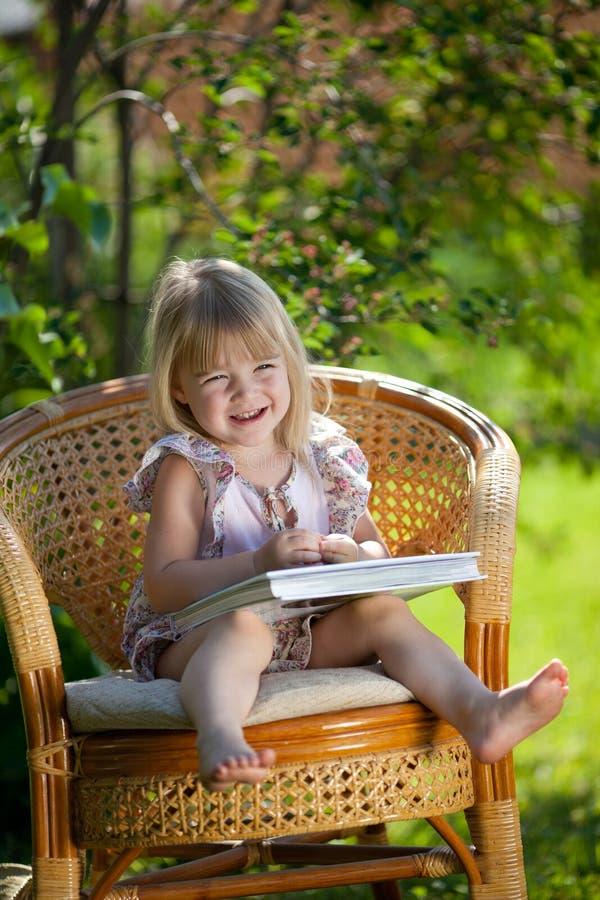 девушка стула книги меньший напольный wicker чтения стоковое изображение rf