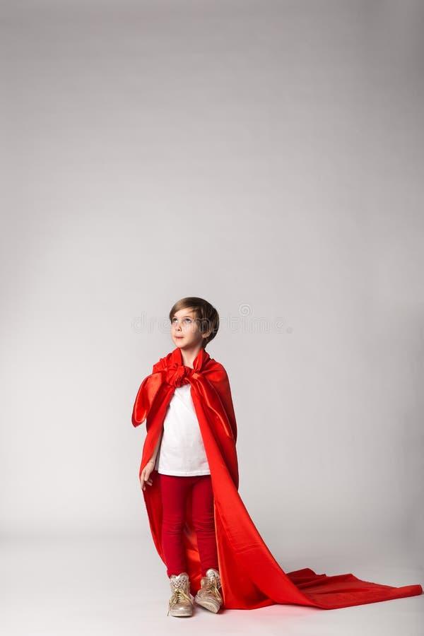 Девушка супергероя в красной накидке представляя в студии стоковые фото