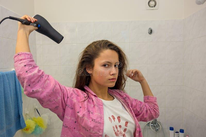 Девушка сушит ее волосы стоковое изображение