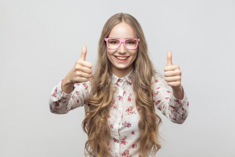 Девушка счастья белокурая в солнечных очках, показывающ большие пальцы руки вверх, смотря стоковые изображения rf