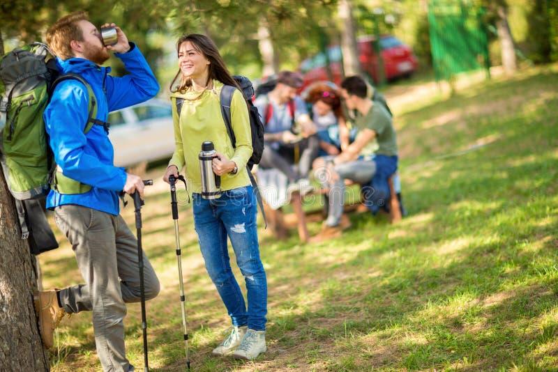 Девушка счастлива когда см. мужского друга пока питьевая вода в передней части стоковое изображение rf