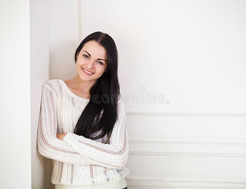 Девушка счастливого брюнет предназначенная для подростков около стены в комнате стоковые изображения rf