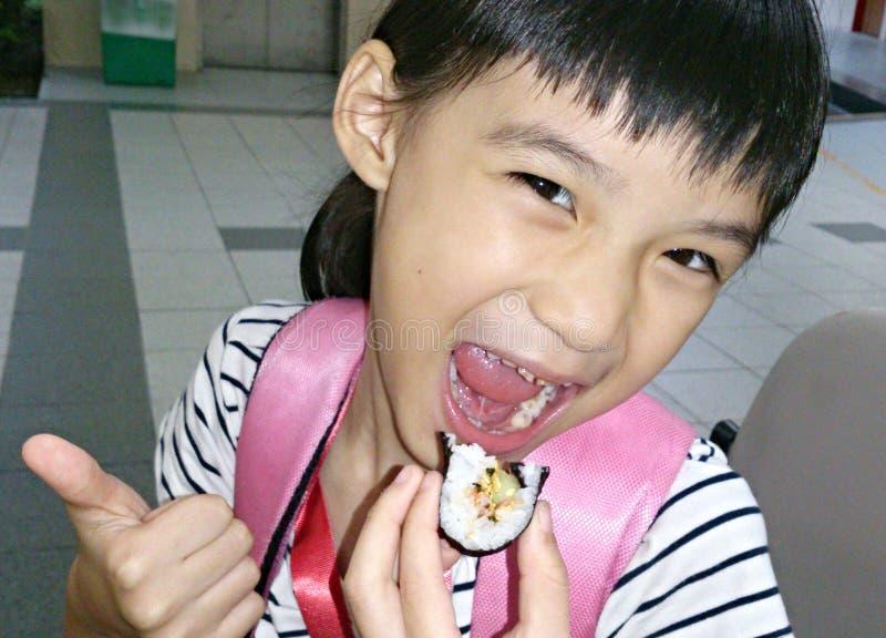 Девушка счастливо есть суши
