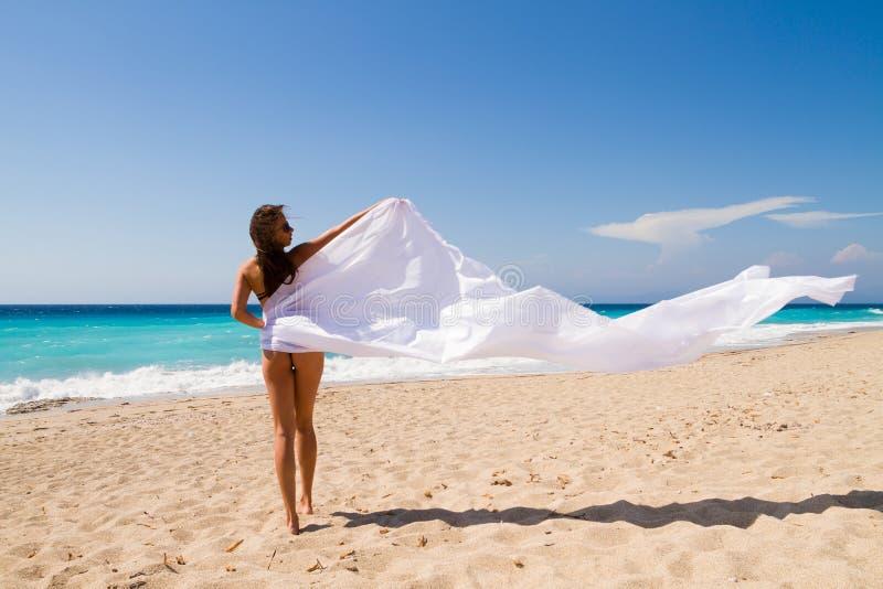 Девушка с белым саронгом на пляже. стоковые фотографии rf