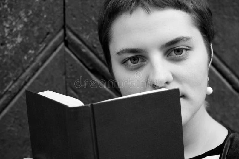 Девушка с большими глазами и короткими волосами прячет за книгой Портрет Конца-вверх Пекин, фото Китая светотеневое стоковая фотография rf