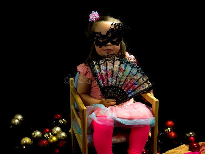 Девушка с вентилятором и маска в платье стоковое изображение