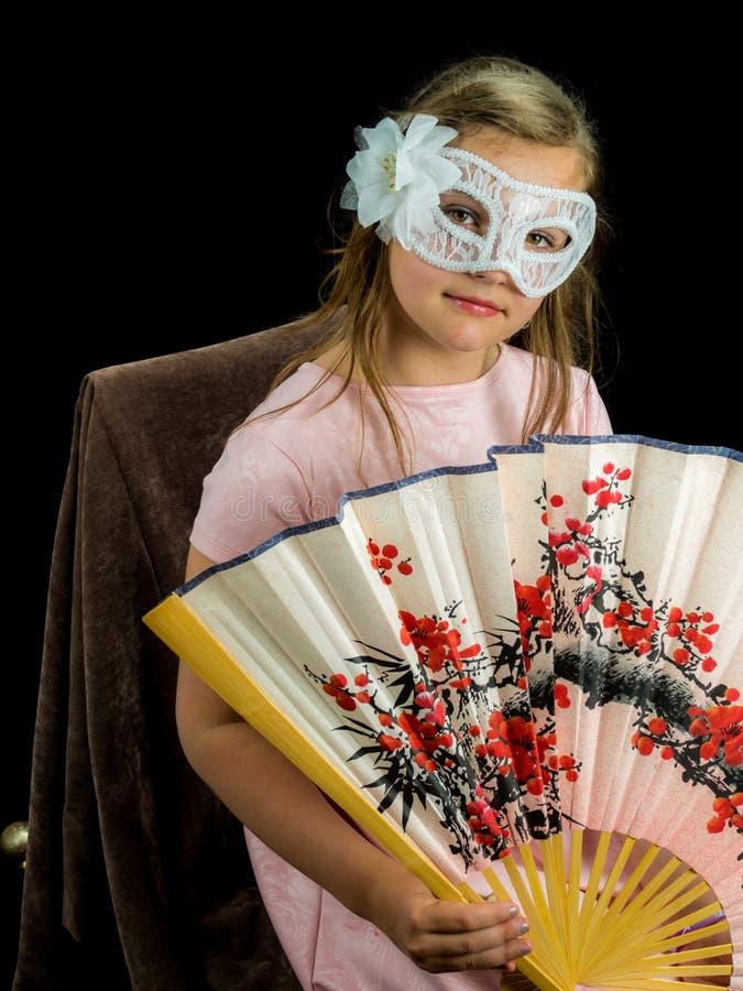 Девушка с вентилятором и маска в платье стоковые изображения rf