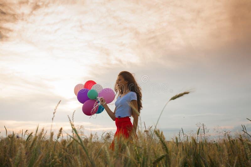 Девушка с воздушными шарами в пшеничном поле стоковое изображение rf