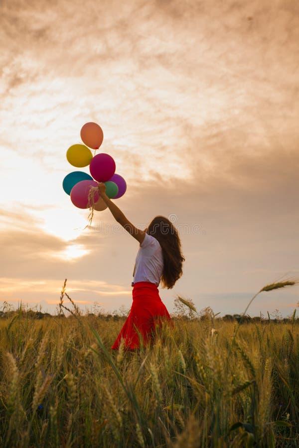 Девушка с воздушными шарами в пшеничном поле стоковая фотография rf