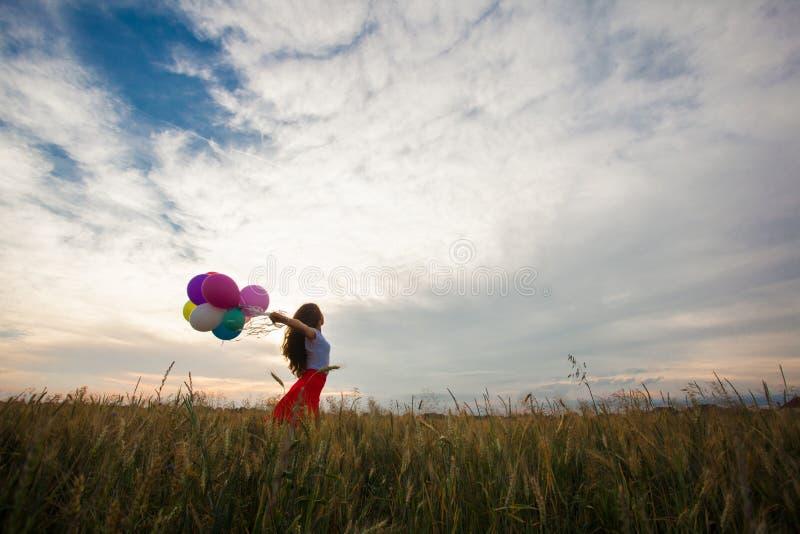 Девушка с воздушными шарами в пшеничном поле стоковые фото