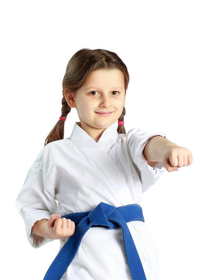 Девушка с голубым поясом удар рука пунша на белой предпосылке стоковая фотография