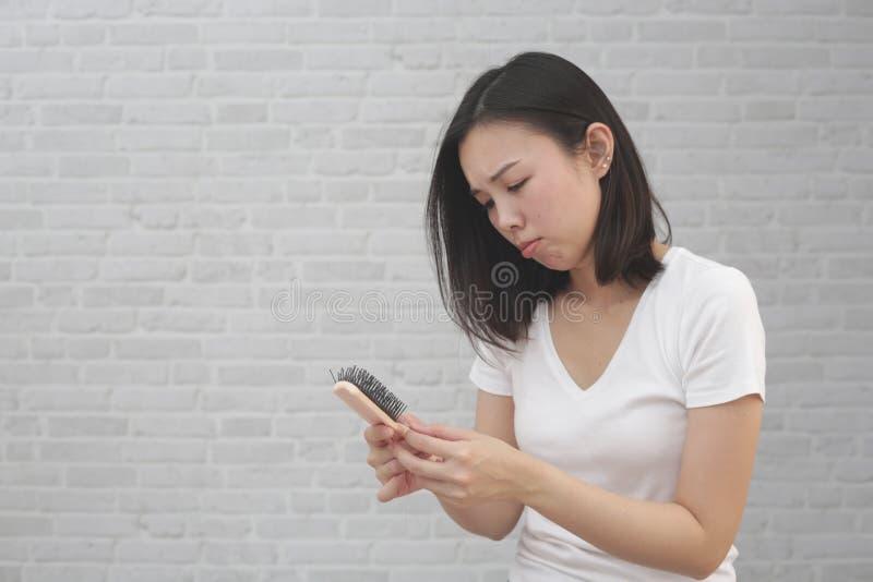 Девушка с гребнем и выпадением волос проблемы на предпосылке стоковая фотография rf