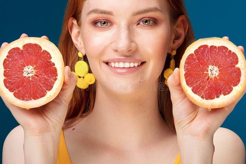 Девушка с грейпфрутом на голубой предпосылке стоковые изображения rf