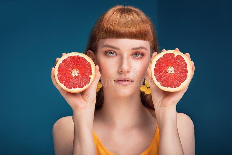 Девушка с грейпфрутом на голубой предпосылке стоковое фото