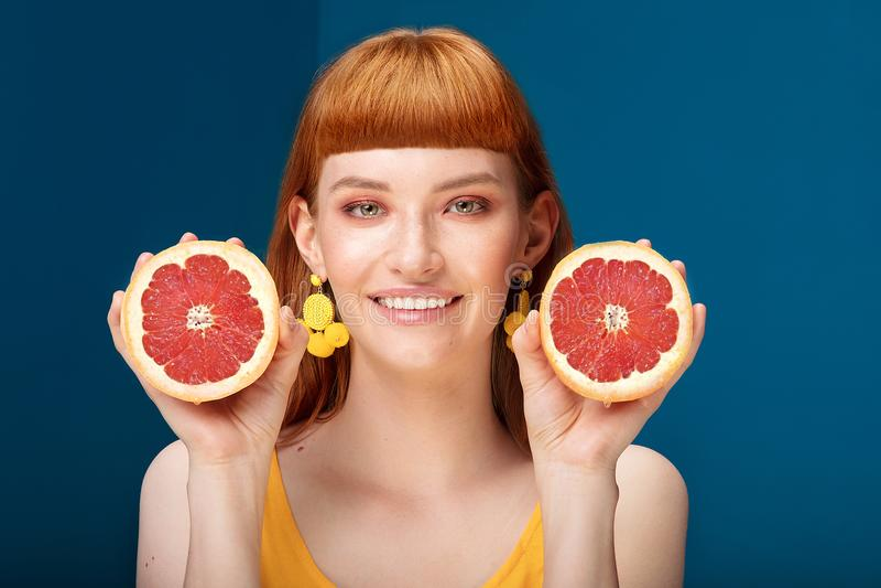 Девушка с грейпфрутом на голубой предпосылке стоковые изображения