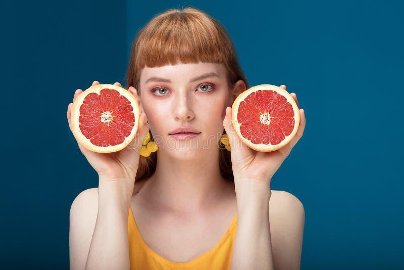 Девушка с грейпфрутом на голубой предпосылке стоковые фото