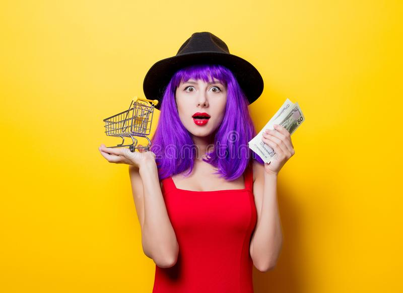 Девушка с деньгами и магазинной тележкаой стоковые фото
