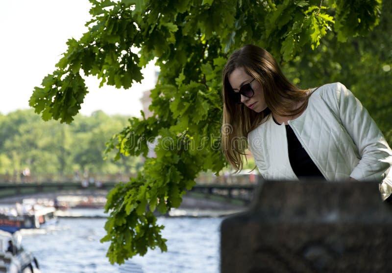 Девушка с длинными волосами в белой куртке среди растительности на стоковые изображения