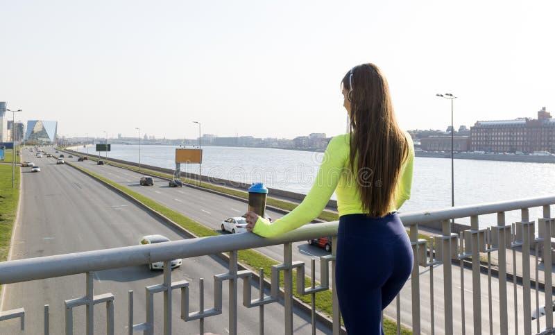 Девушка с длинными волосами в sporty зеленые верхние стойки на мосте над дорогой с двигая автомобилями стоковая фотография