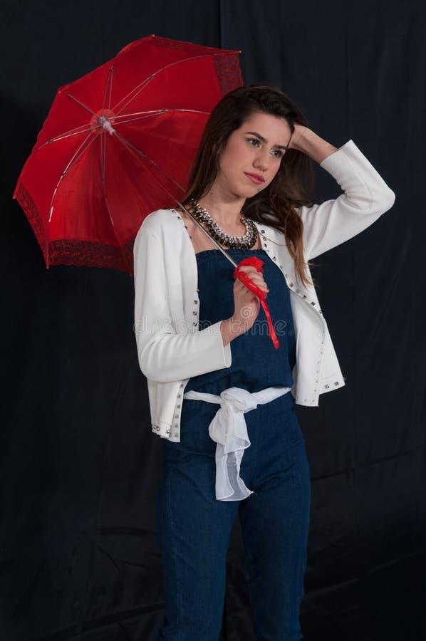 Девушка с длинными коричневыми волосами, одетое ультрамодное с белым свитером блейзера и прозодежды джинсовой ткани Он держит кра стоковое изображение
