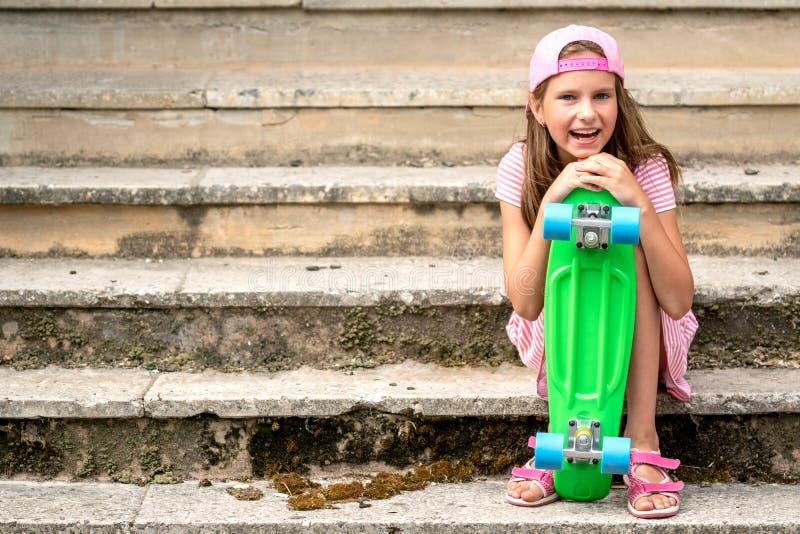 Девушка с доской конька сидит на лестнице стоковые изображения