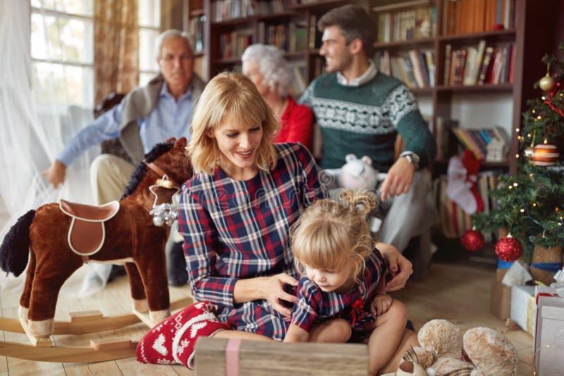 Девушка с ее мамой раскрывает подарок на рождество стоковые изображения