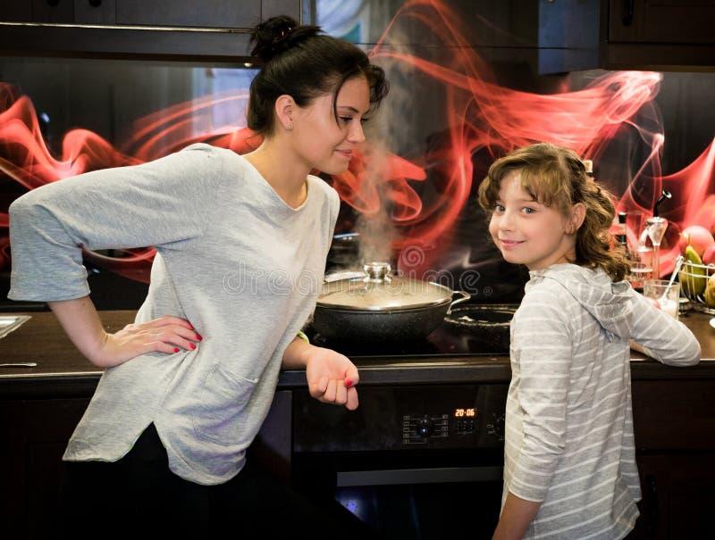 Девушка с ее матерью в кухне на плите стоковые фотографии rf