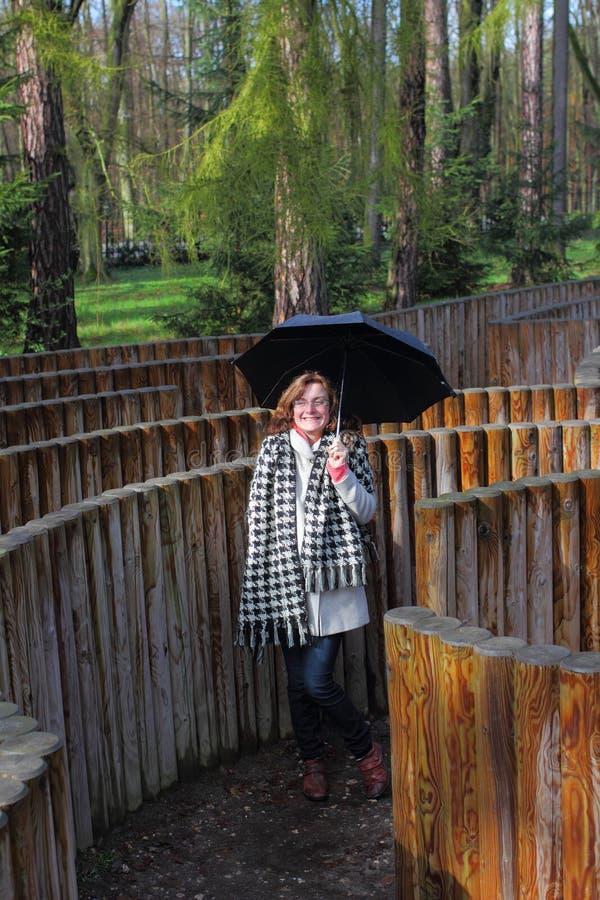 Девушка с зонтиком в лабиринте стоковые изображения rf